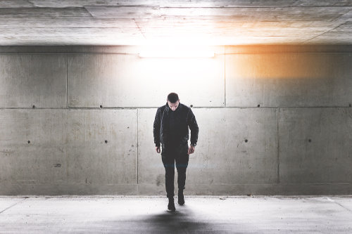 Mężczyzna w oświetlonym garażu wykonuje krok