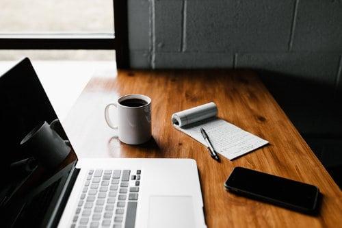 Laptop, telefon komórkowy i kubek z kawą na biurku