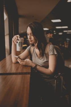 Kobieta w kawiarni pisze coś w smartphonie