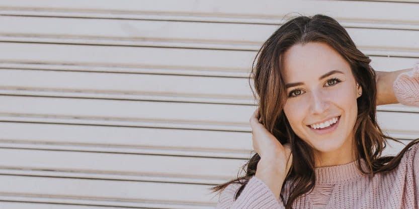 Kobieta wswetrze podtrzymuje z tyłu włosy i się uśmiecha