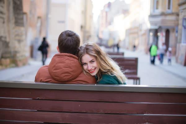 Kobieta siedzi z partnerem na ławce i się uśmiecha