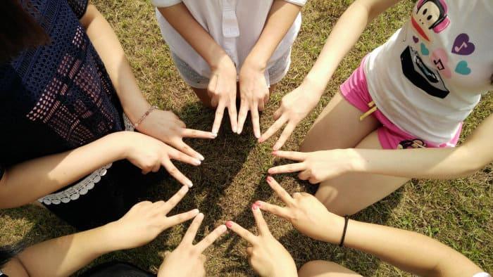 Kobiety siedzą w kręgu i stykają się dłońmi