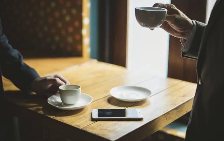 Dwoje znajomych pije kawę w filiżankach