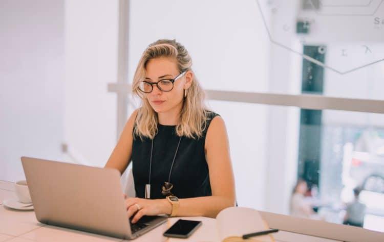 Blondynka w okularach pracuje przy laptopie