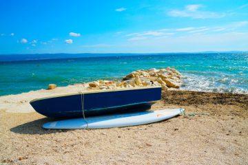 Łódka i deska surfingowa nad morzem